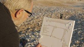 Starszy mężczyzna maluje obrazek na plaży Nad ramię strzałem starszy męski artysta stosuje białą farbę kanwa zbiory wideo