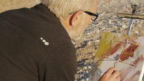 Starszy mężczyzna maluje obrazek na plaży Nad ramię strzałem starszy męski artysta stosuje farbę kanwa z a zbiory wideo