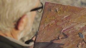 Starszy mężczyzna maluje obrazek na plaży Nad ramieniem strzelał starszy męski artysta stosuje akrylową farbę kanwa zbiory wideo
