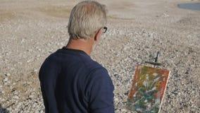 Starszy mężczyzna maluje obrazek na plaży Tylny widok starszy męski artysta gestykuluje patrzejący jego ostatnio malującego zbiory