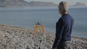 Starszy mężczyzna maluje obrazek na plaży Tylny widok starszy męski artysta patrzeje jego ostatnio malującego dalej obrazek zbiory wideo