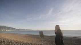 Starszy mężczyzna maluje obrazek na plaży Tylny widok starszy męski artysta patrzeje jego ostatnio malującego dalej obrazek zdjęcie wideo