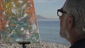 Starszy mężczyzna maluje obrazek na plaży W górę starszego męskiego artysty patrzeje jego ostatnio malującego w szkłach zbiory
