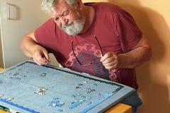 Starszy mężczyzna na jego swój trudnym robić wyrzynarki łamigłówce Zdjęcie Stock