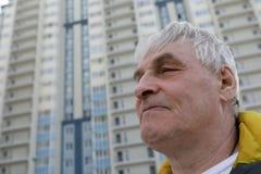 Starszy mężczyzna na nowym budynku tle Zdjęcia Royalty Free