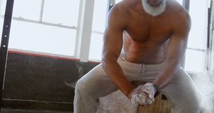 Starszy mężczyzna naciera bielu proszek na jego ręce przed treningiem 4k zbiory