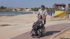 Starszy mężczyzna niesie kobiety w wózku inwalidzkim wzdłuż morza zbiory