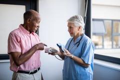 Starszy mężczyzna opowiada fabrykować podczas gdy wskazujący przy ciśnieniem krwi obraz royalty free