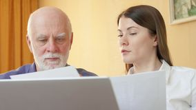 Starszy mężczyzna opowiada pieniężny doradca Żeński konsultant wyjaśnia starszego klienta jego plan emerytalny zdjęcie wideo
