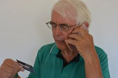 Starszy mężczyzna płaci z kartą kredytową nad telefonem fotografia royalty free