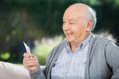 Starszy mężczyzna Patrzeje karty Podczas gdy Siedzący Na leżance fotografia royalty free