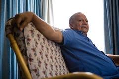 Starszy mężczyzna patrzeje oddalony podczas gdy relaksujący na kanapie przy emerytura domem Zdjęcia Stock