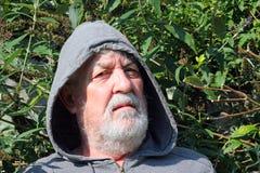 Starszy mężczyzna patrzeje poważny w kapiszonie z bliska Zdjęcie Royalty Free