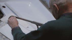Starszy mężczyzna piłuje plastikowego baru z ręką zobaczył zbiory