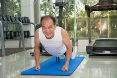 Starszy mężczyzna podnosi w sprawności fizycznej centrum, sporcie i zdrowia pojęciu, sprawność fizyczna ćwiczy pcha robić Fotografia Royalty Free