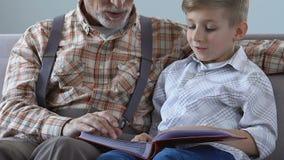 Starszy mężczyzna pokazuje albumowego fotografia wnuka, mówi życiową historię, rodzinna bliskość zbiory