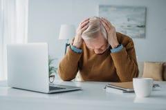 Starszy mężczyzna pracuje w biurze i cierpieć obraz royalty free