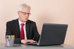 Starszy mężczyzna przy biurem Zdjęcie Stock
