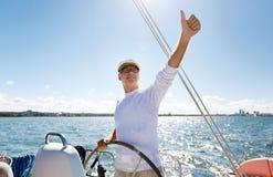 Starszy mężczyzna przy sterem na łodzi lub jachtu żeglowaniu w morzu Obraz Stock