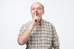 Starszy mężczyzna robi cisza gestowi, utrzymuje je w sekrecie fotografia stock