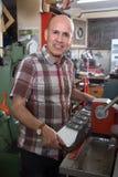 Starszy mężczyzna robi pojazd liczbom na maszynie w warsztacie Zdjęcia Royalty Free