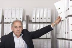 Starszy mężczyzna stawia dokument w półkę Obraz Stock
