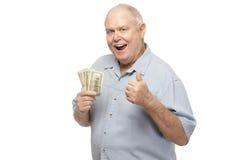 Starszy mężczyzna trzyma dolary i pokazuje aprobaty Fotografia Stock