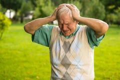 Starszy mężczyzna trzyma jego głowę zdjęcia stock