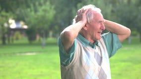 Starszy mężczyzna trzyma jego głowę zdjęcie wideo