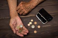 Starszy mężczyzna trzyma starej menniczej kiesy i monet Pojęcie ubóstwo w emerytura Zdjęcie Stock