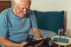 Starszy mężczyzna używa cyfrową pastylkę obrazy royalty free