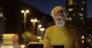 Starszy mężczyzna używa cyfrową pastylkę blisko ulicy 4k zbiory wideo