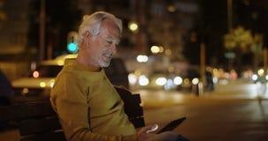Starszy mężczyzna używa cyfrową pastylkę blisko ulicy 4k zbiory