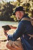Starszy mężczyzna używa cyfrową zakładkę w lesie dla nawigaci Obrazy Royalty Free