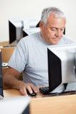 Starszy mężczyzna Używa komputer Przy biurkiem W sala lekcyjnej zdjęcia stock