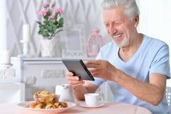 Starszy mężczyzna używa pastylkę podczas gdy pijący herbaty fotografia stock