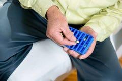 Starszy mężczyzna używa pigułka organizatora obraz stock