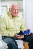 Starszy mężczyzna używa pigułka organizatora Obrazy Stock