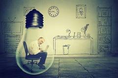 Starszy mężczyzna używa pracować na komputerowym obsiadaniu wśrodku elektrycznej lampy w korporacyjnym biurze fotografia stock