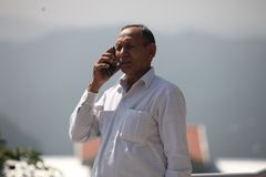 Starszy mężczyzna używa smartphone na jego domowym dachu fotografia stock