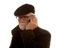 Starszy mężczyzna w Flatcap opowiada na telefonie komórkowym zdjęcie stock