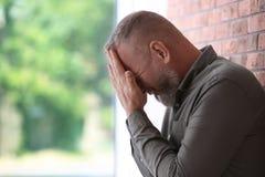 Starszy mężczyzna w stanie depresja blisko ściana z cegieł zdjęcia royalty free