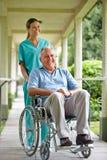 Starszy mężczyzna w wózek inwalidzki z pielęgniarką Fotografia Stock