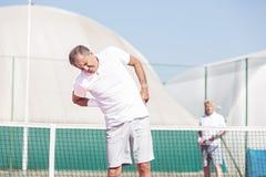Starszy mężczyzna z backache podczas gdy stojący przeciw przyjacielowi podczas tenisa dopasowania na słonecznym dniu fotografia royalty free