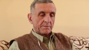 Starszy mężczyzna z białym smartphone siedzi na leżance i słucha muzyka zbiory