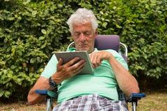 Starszy mężczyzna z cyfrową pastylką Obrazy Stock