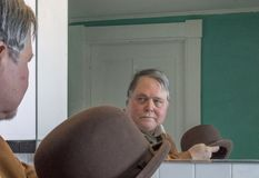 Starszy mężczyzna z Derby kapeluszowy patrzeć w lustro zdjęcia stock