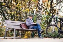 Starszy mężczyzna z electrobike obsiadaniem na ławce outdoors w miasteczku, używać laptop obraz stock