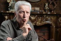 Starszy mężczyzna z fi, cisza, nger na wargach gestykuluje ciszę zdjęcie royalty free