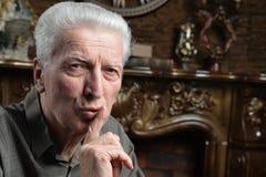 Starszy mężczyzna z gestykuluje ciszę, cisza, palec na wargach obrazy royalty free